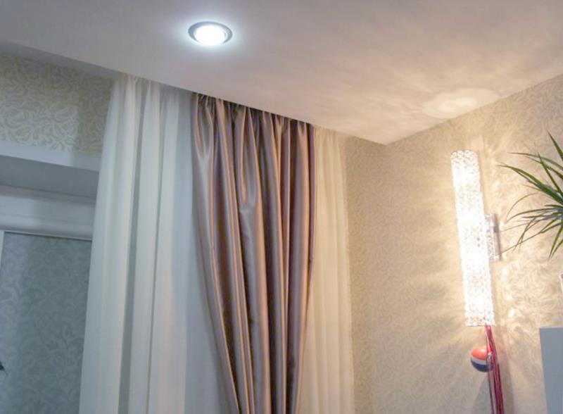 Если в комнате установлен натяжной потолок, то монтаж карниза возможен в нишу, поэтому, кажется, что шторы свисают прямо с потолка.